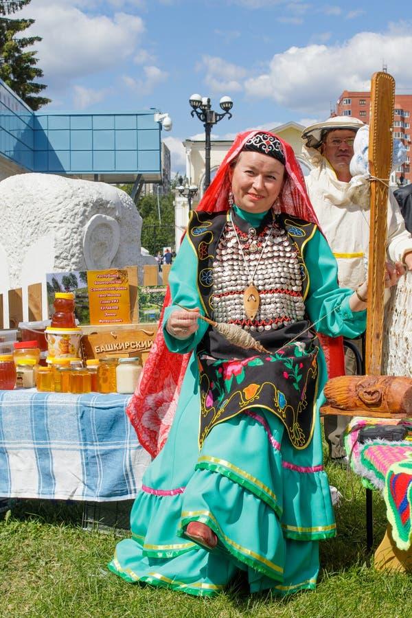 Una mujer en ropa bashkir es que sienta y de giro de las lanas Festividad nacional tradicional Sabantuy en el parque de la ciudad imagen de archivo libre de regalías