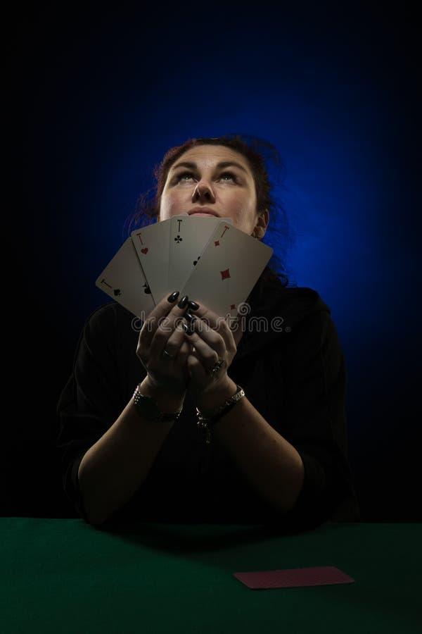 Una mujer en ropa negra sostiene una cubierta de tarjetas imágenes de archivo libres de regalías