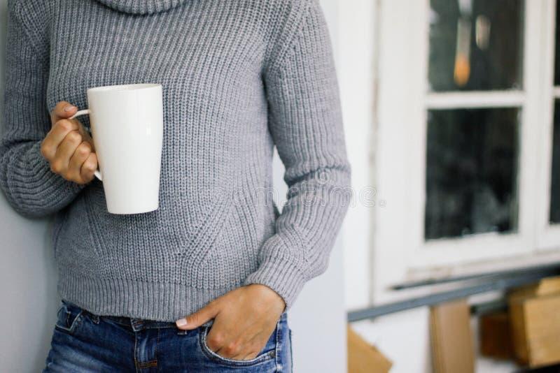Una mujer en un suéter gris caliente se coloca en la ventana de madera y sostiene una taza blanca en sus manos Estilo casual fotografía de archivo libre de regalías