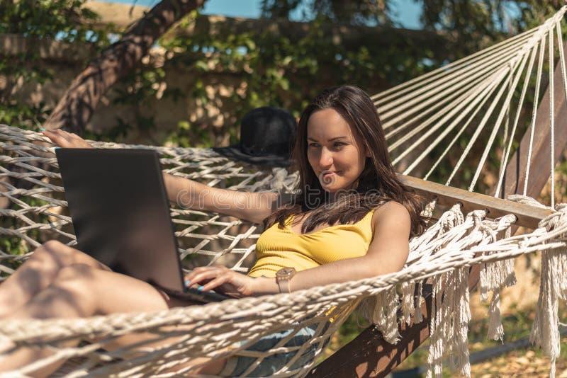 Una mujer en un traje de baño amarillo que miente en una hamaca usando un ordenador portátil fotografía de archivo