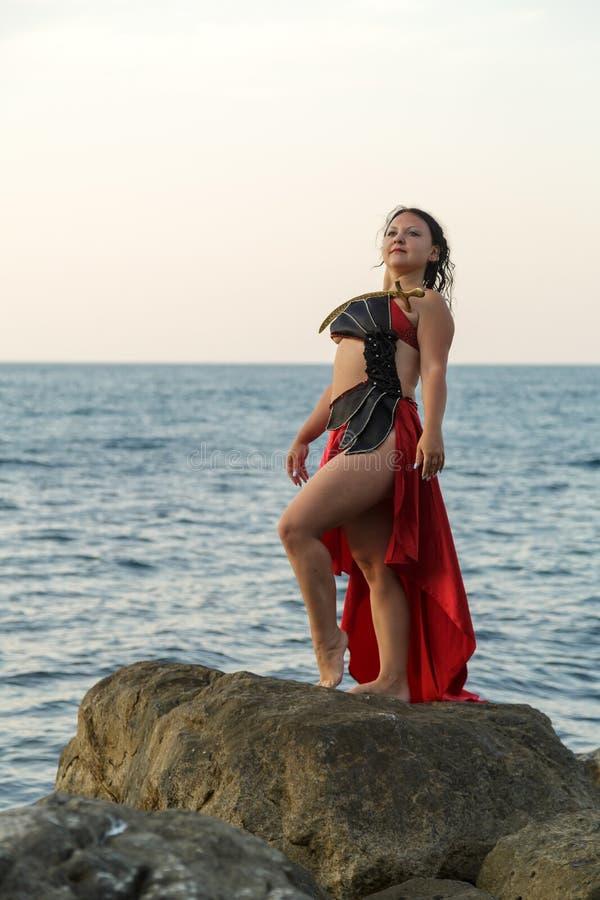 Una mujer en un traje rojo de la danza con un sable en sus actitudes del pecho en una roca lavada por las ondas del mar imagen de archivo