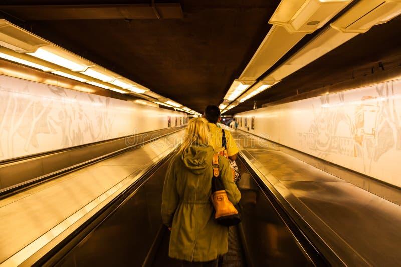 Una mujer en un travellator en el sistema del subterráneo en Sydney fotos de archivo