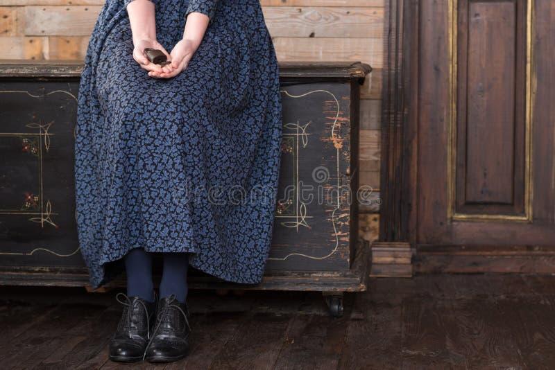 Una mujer en un vestido azul largo se está sentando en un pecho negro y está sosteniendo una cerradura vieja con una llave fotografía de archivo