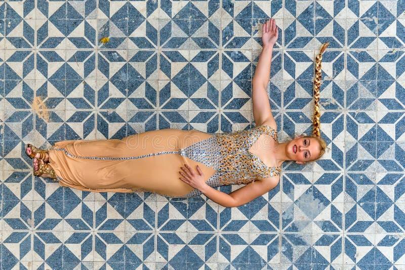 Una mujer en un vestido festivo en un castillo abandonado El modelo está en el piso fotos de archivo libres de regalías