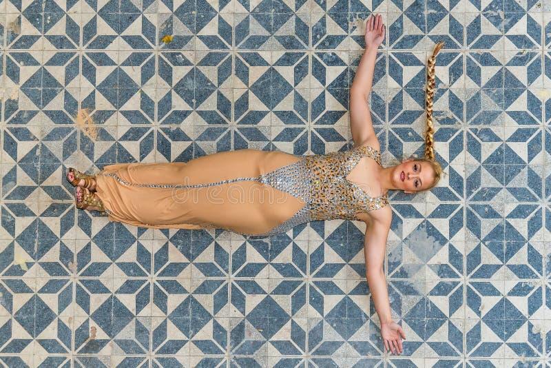 Una mujer en un vestido festivo en un castillo abandonado El modelo está en el piso foto de archivo libre de regalías