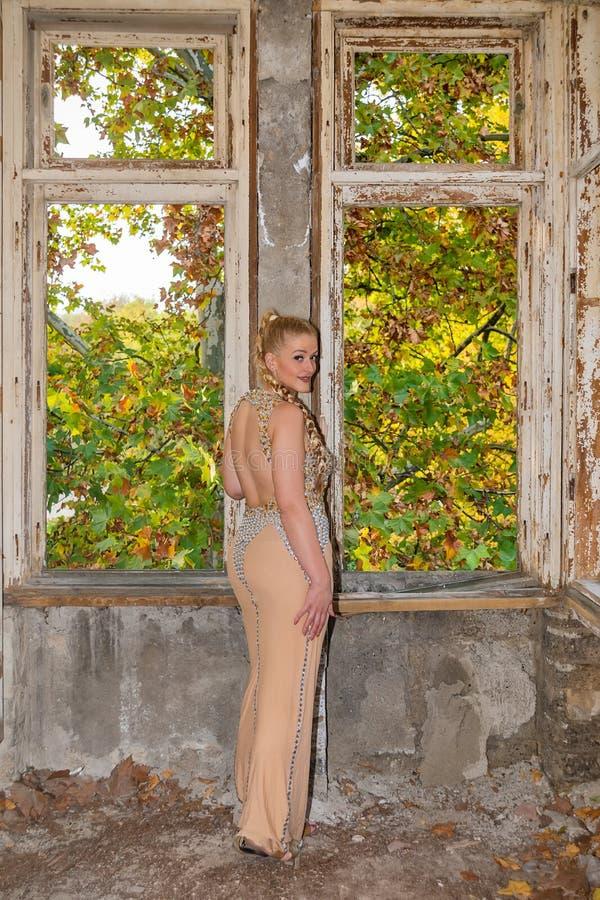 Una mujer en un vestido festivo en un castillo abandonado El modelo femenino presenta al lado de la puerta abandonada foto de archivo libre de regalías