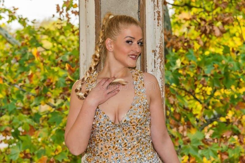 Una mujer en un vestido festivo en un castillo abandonado El modelo femenino presenta al lado de la puerta abandonada fotografía de archivo libre de regalías