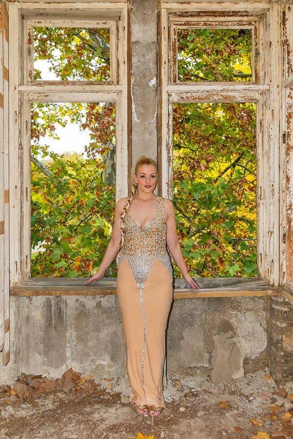 Una mujer en un vestido festivo en un castillo abandonado El modelo femenino presenta al lado de la ventana sin el vidrio fotografía de archivo