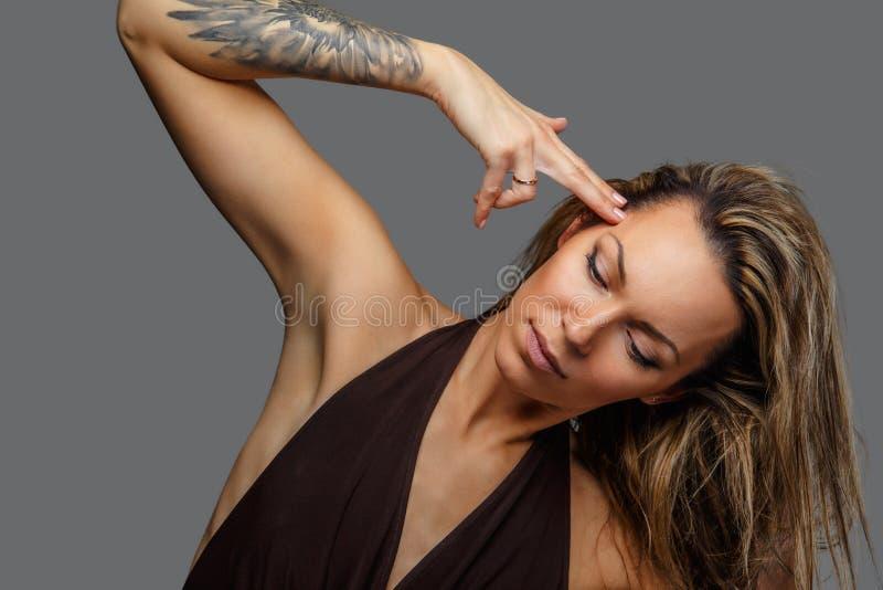 Una mujer en un vestido marrón con el tatuaje en su mano fotos de archivo