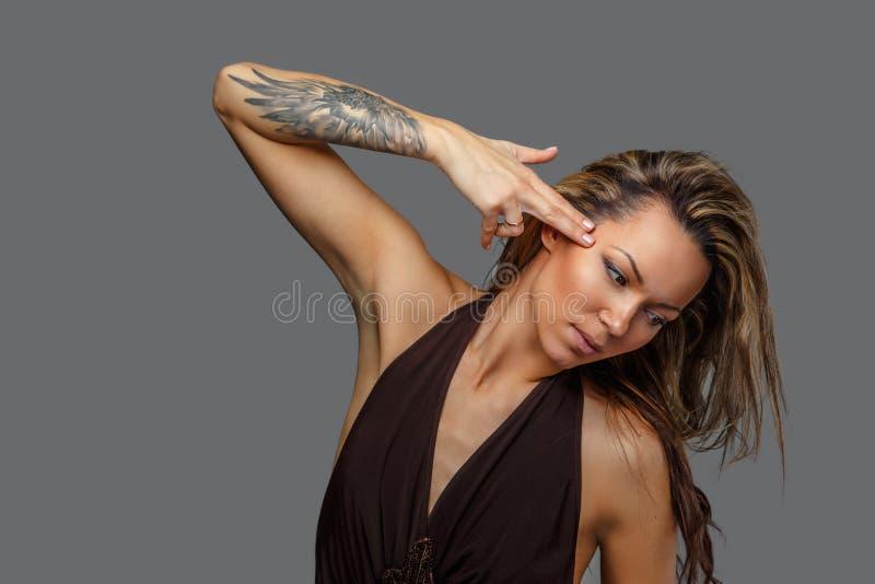 Una mujer en un vestido marrón con el tatuaje en su mano imagen de archivo