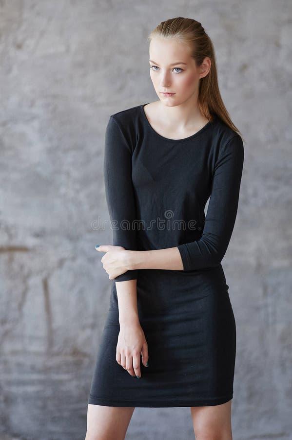 Una mujer en un vestido negro fotos de archivo