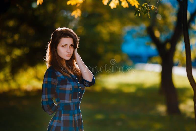 Una mujer en vestido a cuadros largo Muchacha romántica en el parque de la primavera Una mujer camina en el parque en una ropa in imagenes de archivo