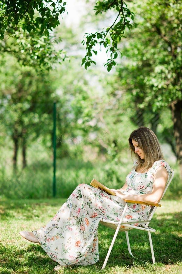 Una mujer en vestido de la flor es libro de lectura en el jard?n - silla de campo imagen de archivo