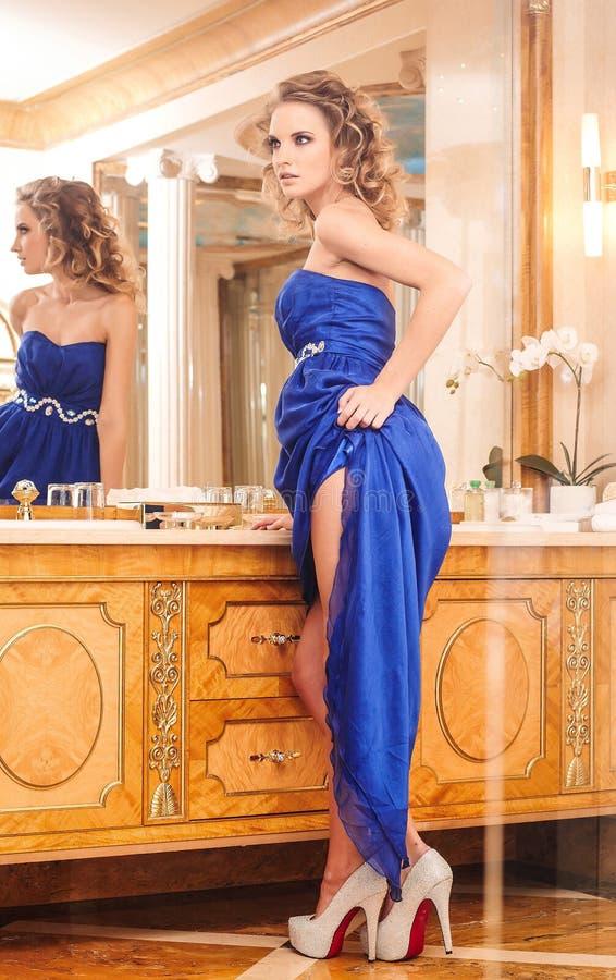 Una mujer encantadora con el peinado rizado elegante que lleva un vestido azul que presenta al lado de un espejo en un cuarto de  fotos de archivo