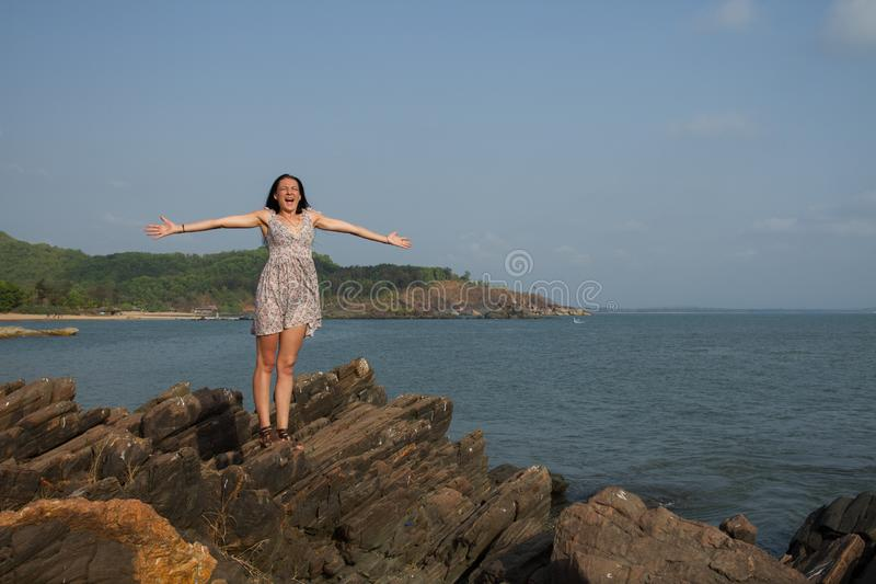 Una mujer es feliz sobre el principio de las vacaciones Una mujer se coloca en una roca con sus brazos extendidos al viento fotos de archivo libres de regalías