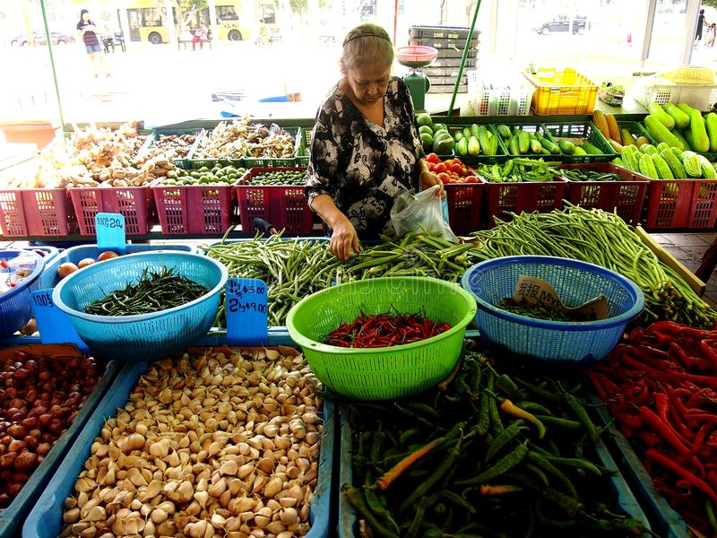 Una mujer escoge las verduras frescas de un mercado en la ciudad de Tampines en Singapur imagenes de archivo