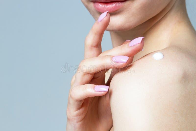 Una mujer está aplicando una crema en su hombro imágenes de archivo libres de regalías