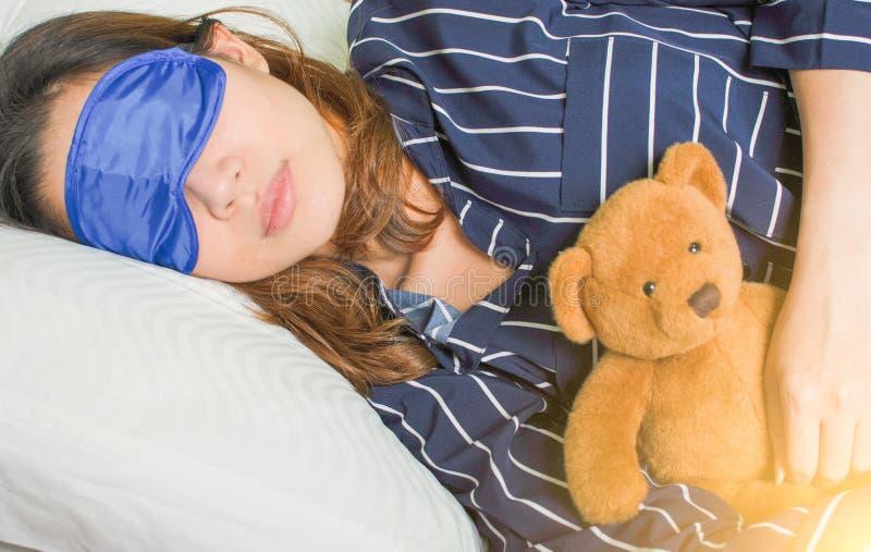 Una mujer está durmiendo en su cama por la mañana fotografía de archivo