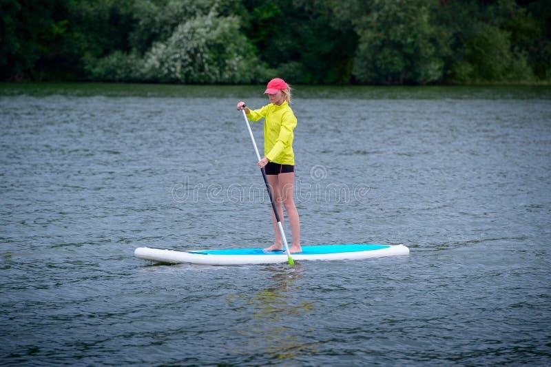 Una mujer está flotando en un tablero del SORBO a lo largo de un río grande Soporte en el embarque de la paleta - actividades al  imagenes de archivo