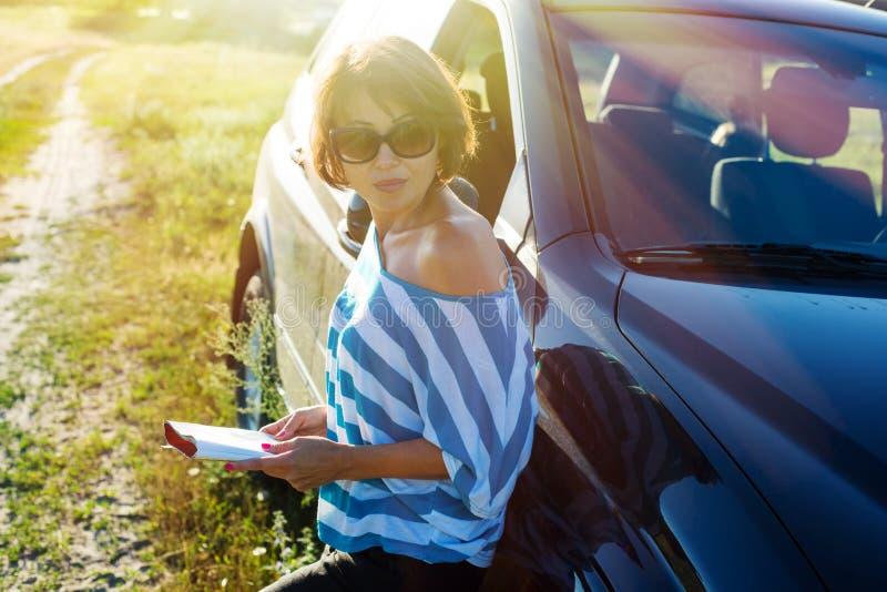 Una mujer está haciendo una pausa el coche en una carretera nacional imagen de archivo