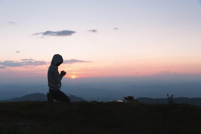Una mujer está rezando a Dios en la montaña Manos rezando con fe en la religión y la creencia en Dios bendiciendo los antecedente fotos de archivo