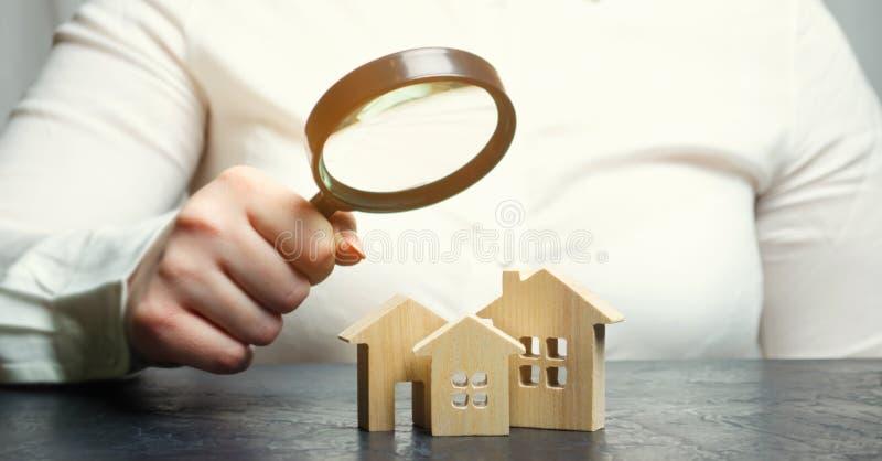 Una mujer está sosteniendo una lupa sobre las casas de madera Tasador de las propiedades inmobiliarias Evaluación/valoración de l fotografía de archivo libre de regalías