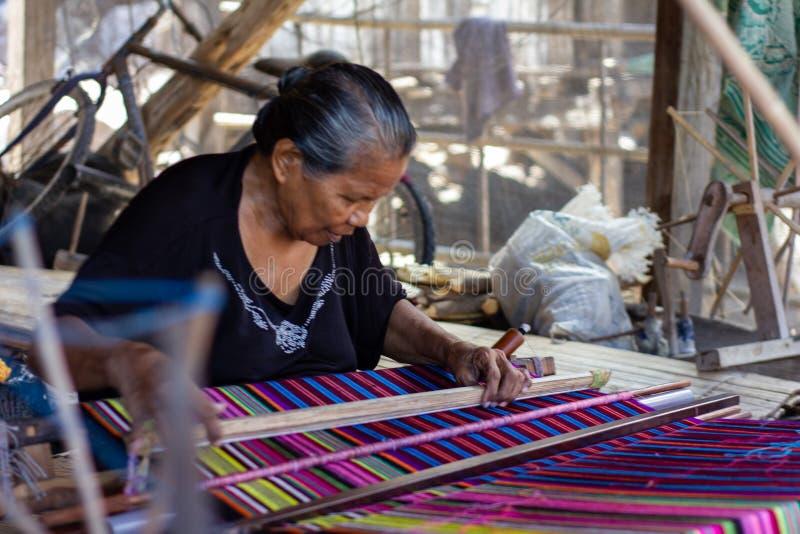 Una mujer está tejiendo telas coloridas tradicionales de Flores Todos los procesos que tejen utilizan el equipo manual y tradicio foto de archivo