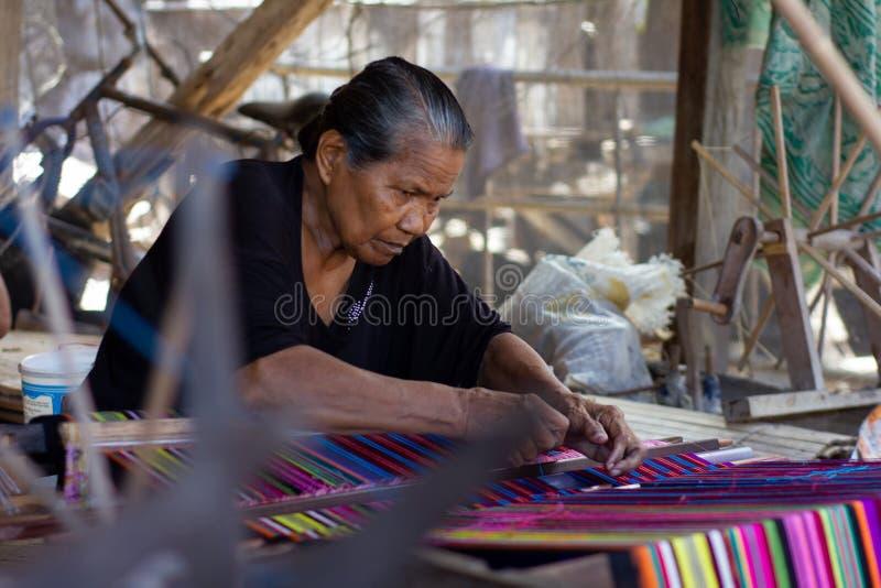 Una mujer está tejiendo telas coloridas tradicionales de Flores Todos los procesos que tejen utilizan el equipo manual y tradicio fotografía de archivo libre de regalías