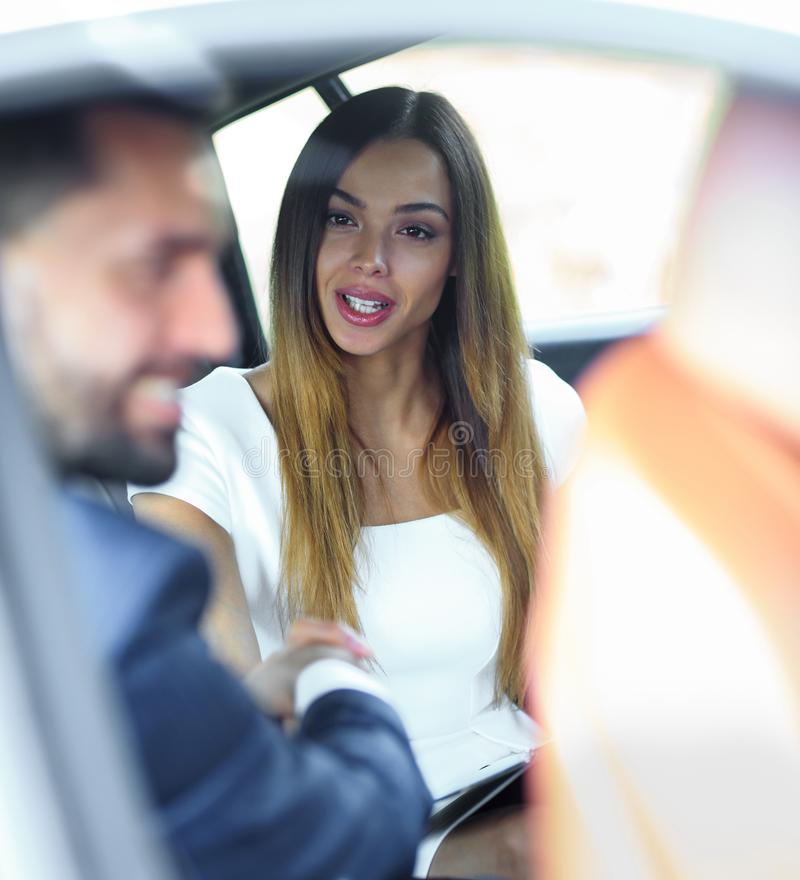 Una mujer está trabajando con una sonrisa atractiva en el coche imagen de archivo libre de regalías