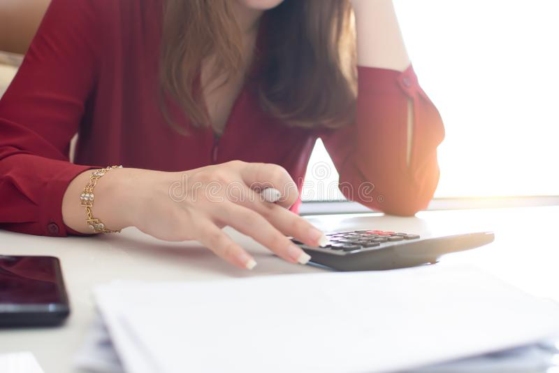 Una mujer está utilizando la calculadora para el trabajo foto de archivo libre de regalías
