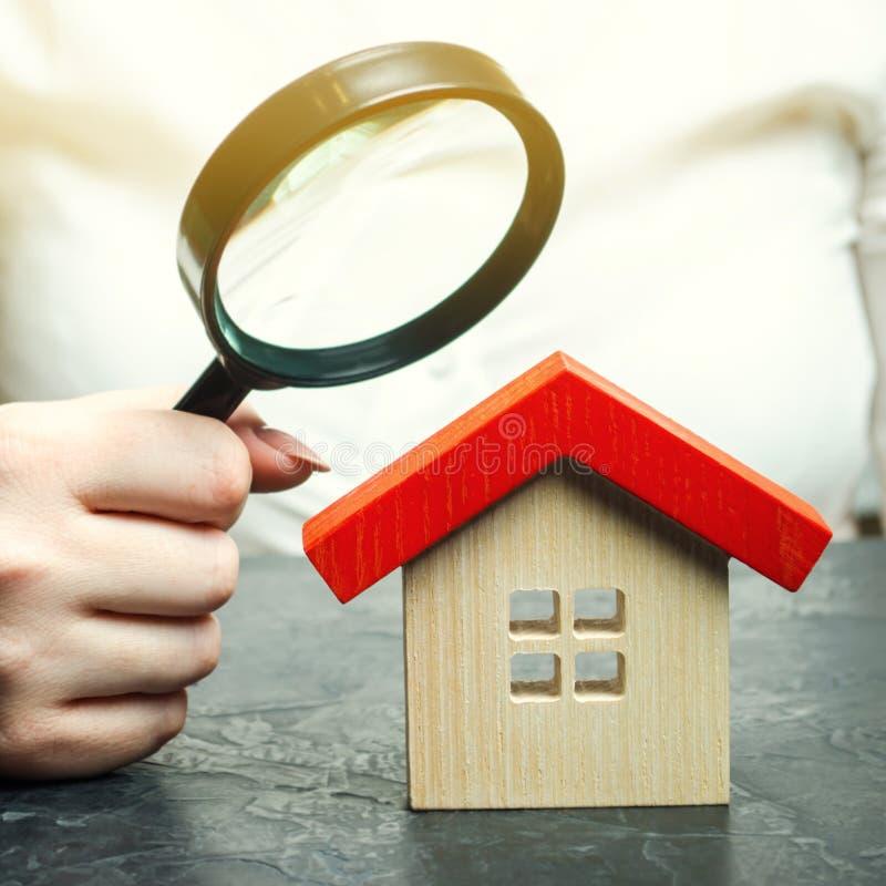 Una mujer est? sosteniendo una lupa sobre una casa de madera Tasador de las propiedades inmobiliarias Evaluaci?n de la condici?n  imagenes de archivo