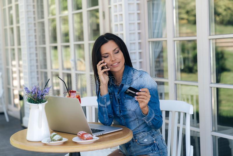 Una mujer europea joven hermosa lleva la ropa elegante, se sienta en una tabla en un café, utiliza un ordenador portátil, bebe de foto de archivo libre de regalías
