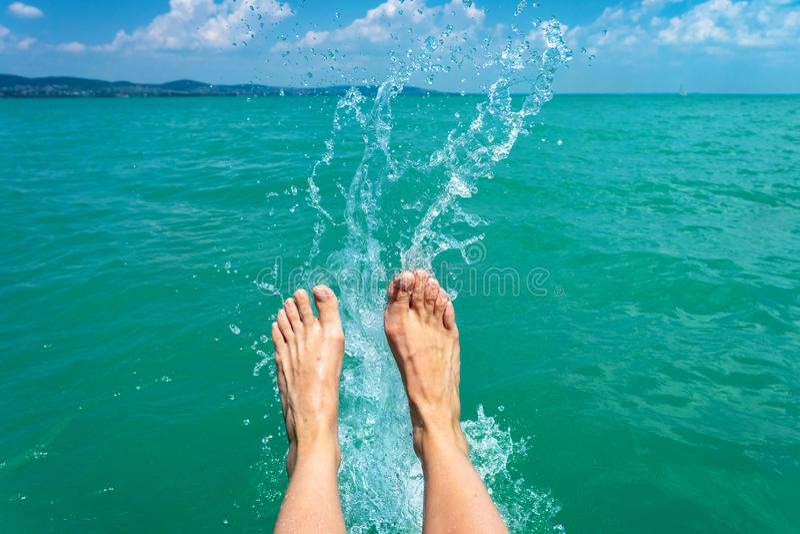 Una mujer feliz de la muchacha está golpeando pies con el pie en un lago del mar y está salpicando el agua en un verano del barco imagenes de archivo