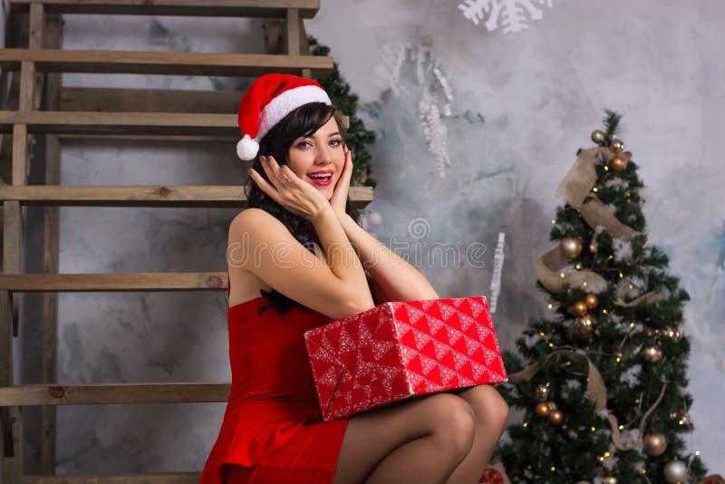 Una mujer feliz joven en el sombrero de santa y en un vestido rojo con una caja g foto de archivo