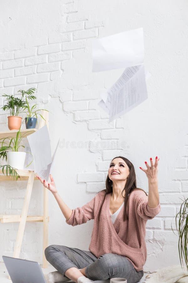 Una mujer feliz joven lanza para arriba un manojo de trozos de papel y los documentos que se sientan cerca del ordenador port?til imagenes de archivo