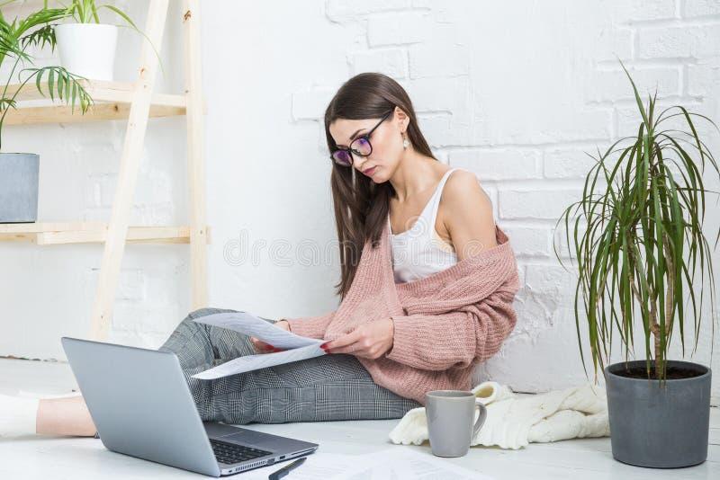 Una mujer feliz joven se sienta en el piso en un apartamento o una oficina brillante interior y trabaja en un ordenador port?til, fotografía de archivo libre de regalías