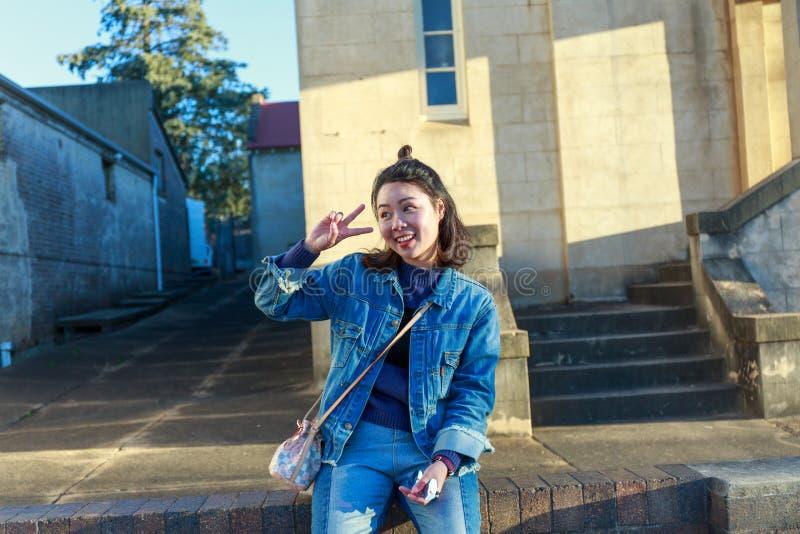 Una mujer feliz que se sienta en la calle con gesto y la sonrisa de mano de la victoria foto de archivo