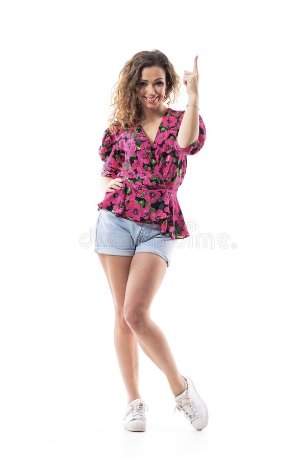 Una mujer feliz, sonriente, apuntando hacia arriba, mirando a la cámara teniendo idea o solución foto de archivo