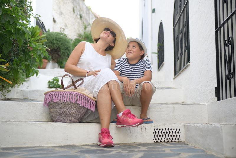 Una mujer feliz y un niño se sientan en las escaleras fotos de archivo