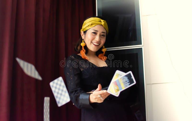 Una mujer gitana está lanzando cartas de tarot fotografía de archivo