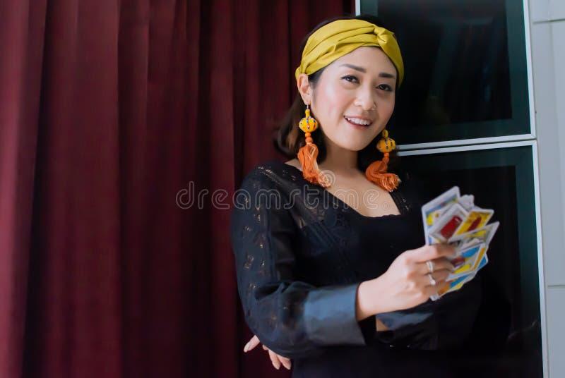 Una mujer gitana o bohemia está sosteniendo cartas de tarot imágenes de archivo libres de regalías