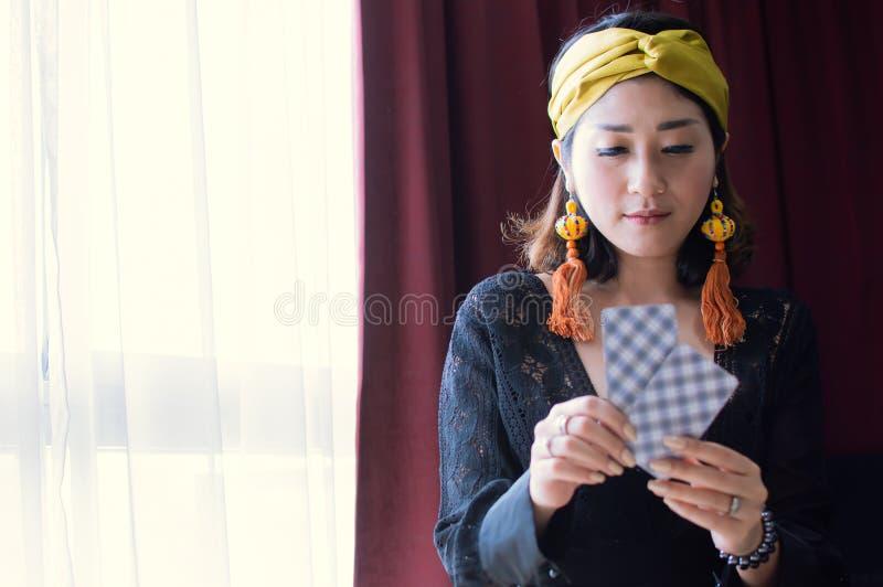 Una mujer gitana o bohemia hermosa está leyendo cartas de tarot imagenes de archivo