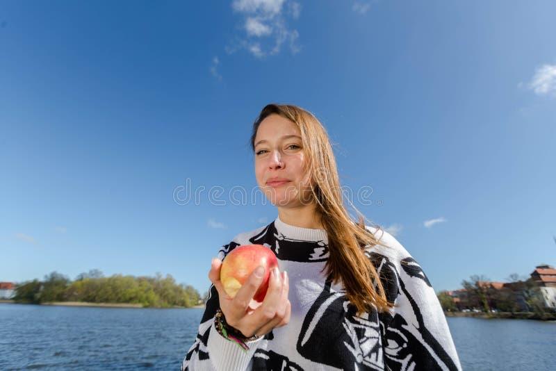Una mujer goza de una manzana imagen de archivo