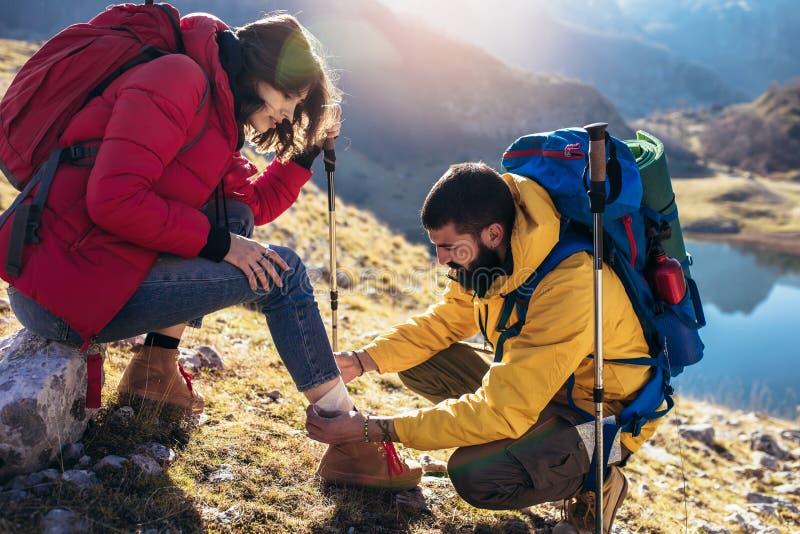Una mujer ha torcido su tobillo mientras que camina, su amigo utiliza el equipo de primeros auxilios imágenes de archivo libres de regalías