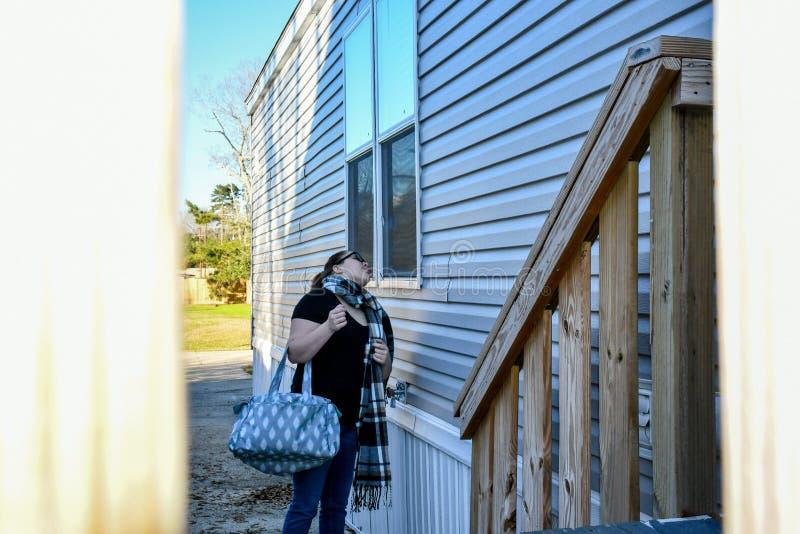 Una mujer hace caras en una ventana de la casa imagenes de archivo