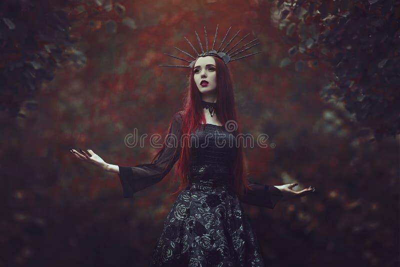 Una mujer hermosa con la piel pálida y el pelo rojo largo en un vestido negro y en el crownk negro Bruja de la muchacha con el va imagen de archivo libre de regalías