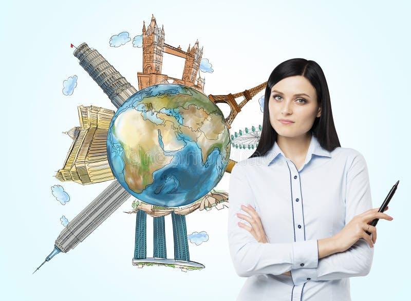 Una mujer hermosa con la pluma de la marca y un globo con los lugares turísticos famosos bosquejados en el mundo Elementos de est fotografía de archivo libre de regalías