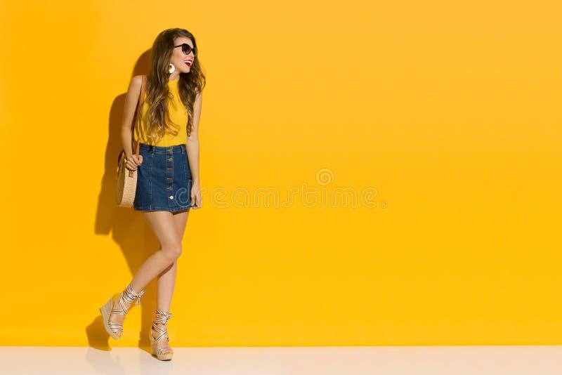 Una Mujer Hermosa Con Minifalda Y Zapatos De Marea Está De Pie Contra La Pared Amarilla foto de archivo