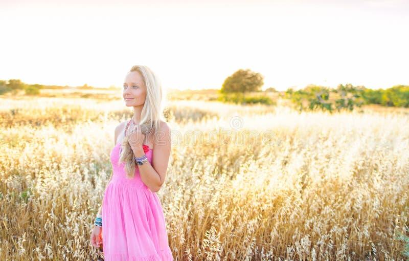 Una mujer hermosa en campo de oro del heno imagen de archivo