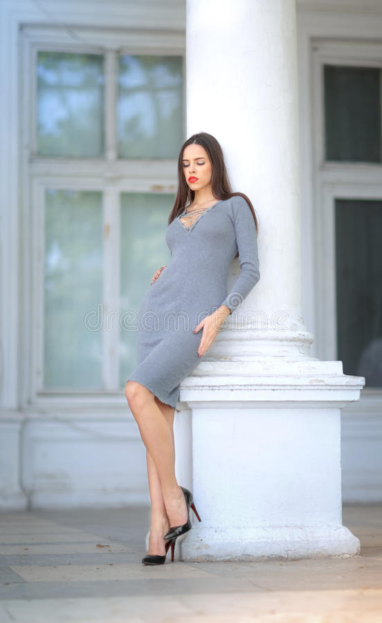 Una mujer hermosa en el fondo de una casa blanca La señora en un vestido y zapatos al aire libre La muchacha cerca de la pizca imágenes de archivo libres de regalías